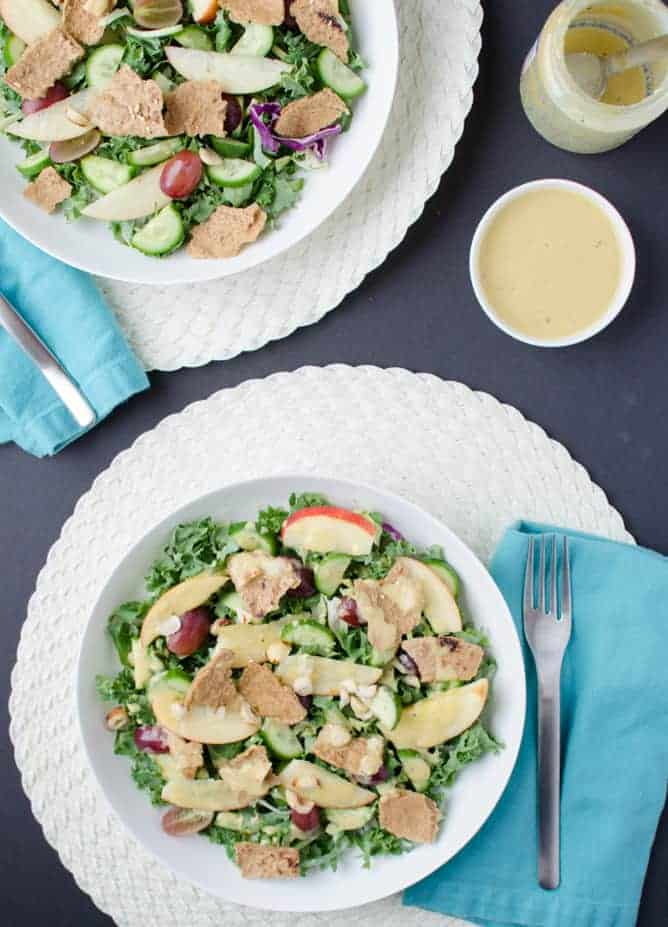 Fall Fattoush Salad! Kale salad tossed with sliced apples, juicy grapes, maple-mustard dressing and topped with pita chips. Vegan and Gluten Free.