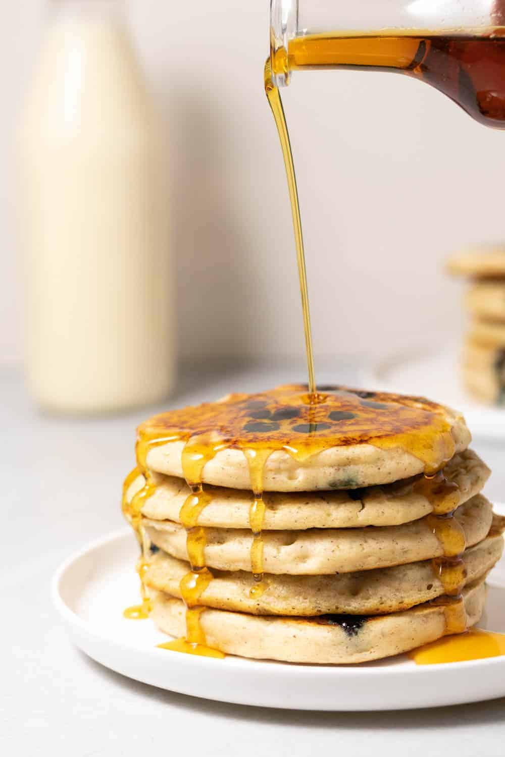 Pouring maple syrup over a stack of fluffy vegan pancakes