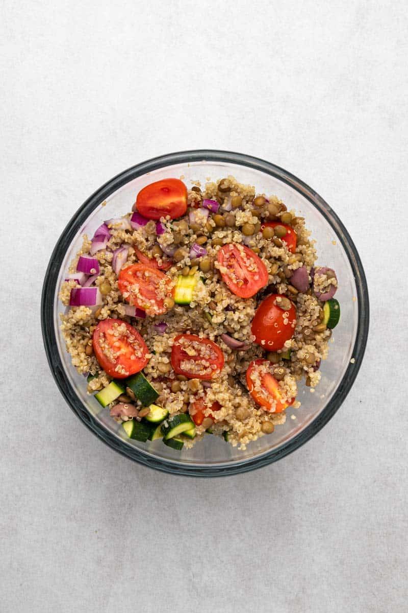 greek lentil salad ingredients tossed in bowl