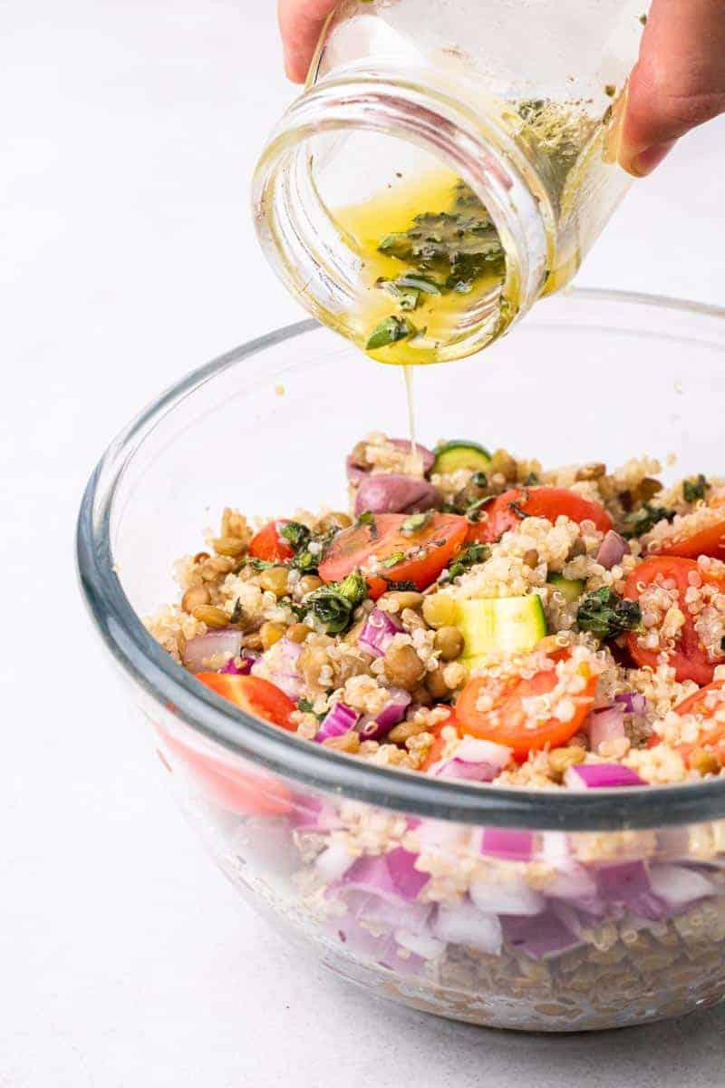 dressing being poured on greek lentil salad