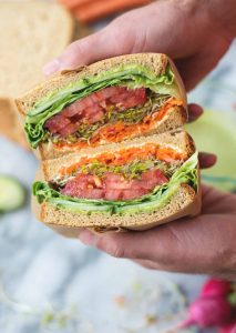 Green Goddess Veggie Sandwich! This sandwich is layered with flavor and packed with vegetables! Homemade green-goddess dressing, tomatoes, sprouts, avocado, goat cheese, radish, carrots. Vegetarian, easily vegan or gluten-free. | www.delishknowledge.com