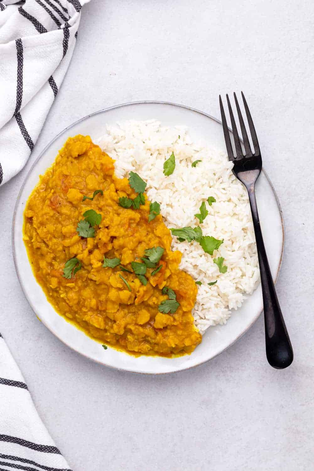 Served dal on white rice with cilantro garnish