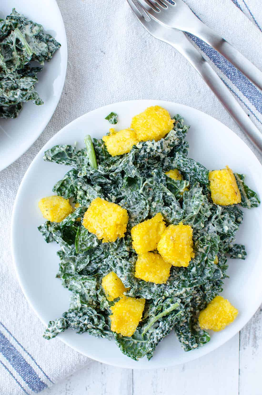 Kale Caesar Salad! Creamy caesar dressing with crispy polenta croutons. Vegan & Gluten-Free | www.delishknowledge.com
