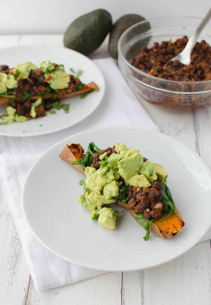 Mexican Stuffed Sweet Potatoes! Baked potatoes stuffed with spinach, spicy black beans, avocado and cilantro. This meal is so filling and packed with nutrition! Gluten free and vegan! | www.delishknowledge.com