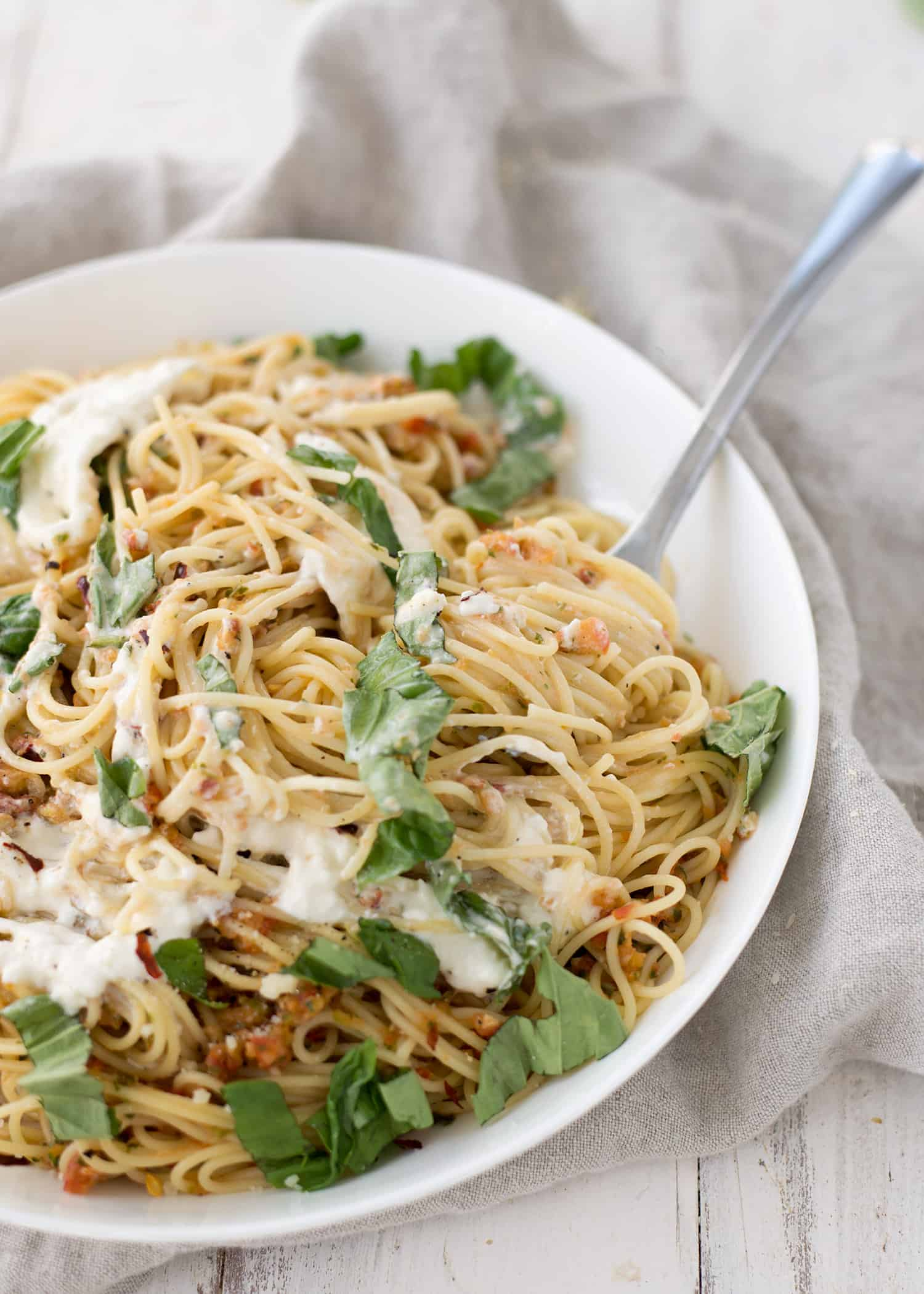 Pasta Checca with Burrata! This recipe is ready in less than 20 minutes. Quick, no-cook sauce tossed with hot angelhair pasta and topped with creamy burrata. Vegetarian. | www.delishknowledge.com