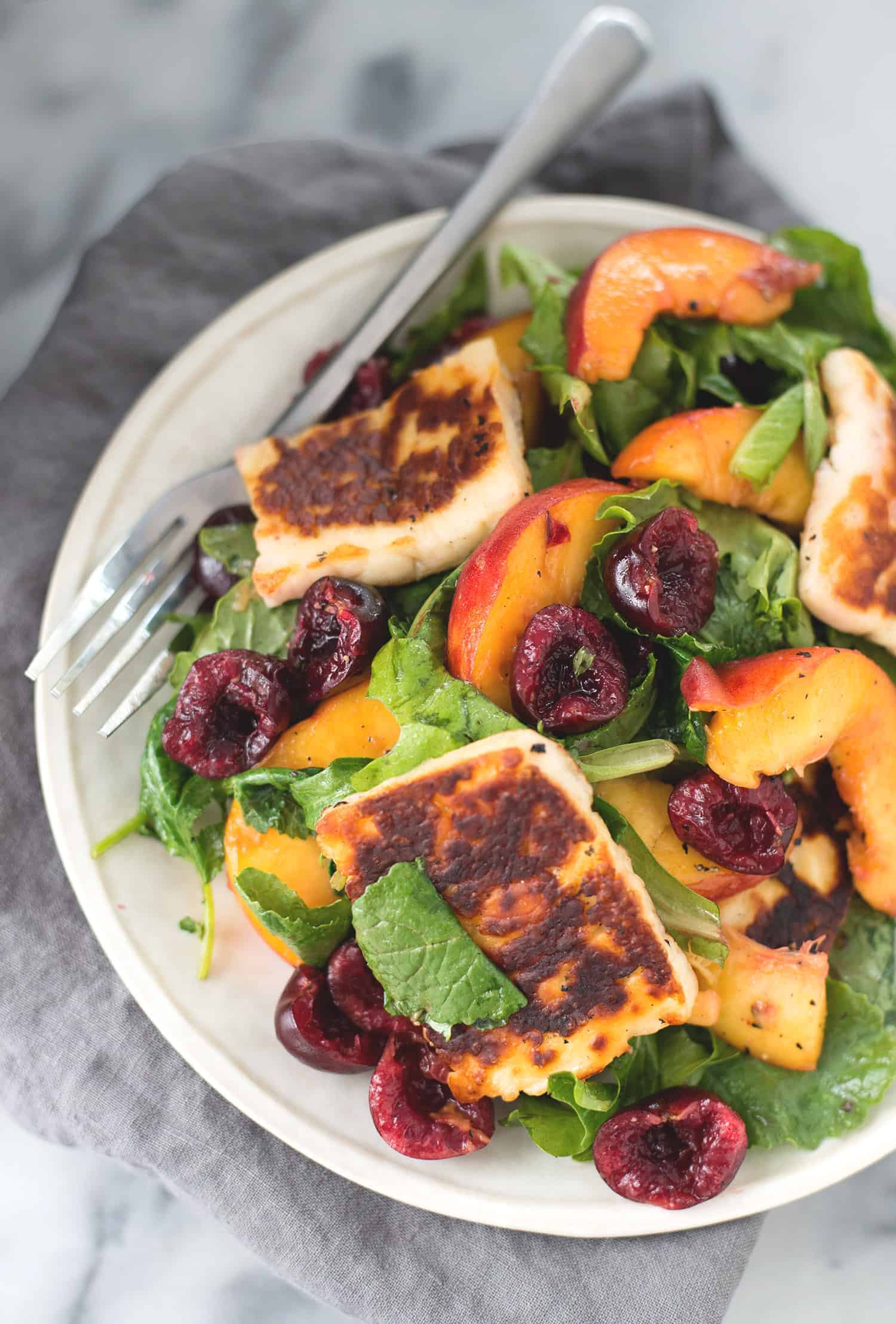 Peach, Cherry and Halloumi Salad! This vibrant salad is perfect for summer. Fresh produce, grilled halloumi cheese, quinoa, pecans and a balsamic vinegar. Vegetarian & Gluten-free | www.delishknowledge.com