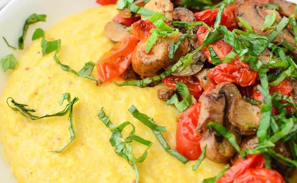Weeknight comfort food! Cheesy polenta bowl topped with roasted tomatoes and mushrooms. Vegan and Gluten-Free. | www.delishknowledge.com