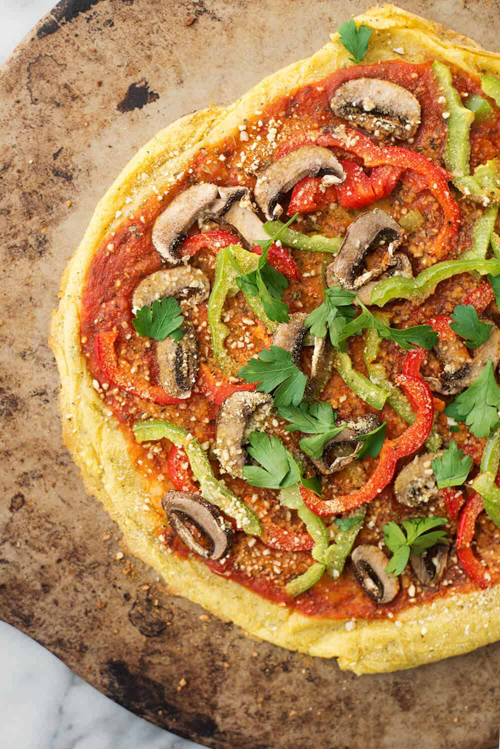 Polenta Pizza! You've got try this unusual twist on pizza. Polenta pizza crust topped with sauce, vegetables and vegan parmesan cheese.| www.delishknowledge.com