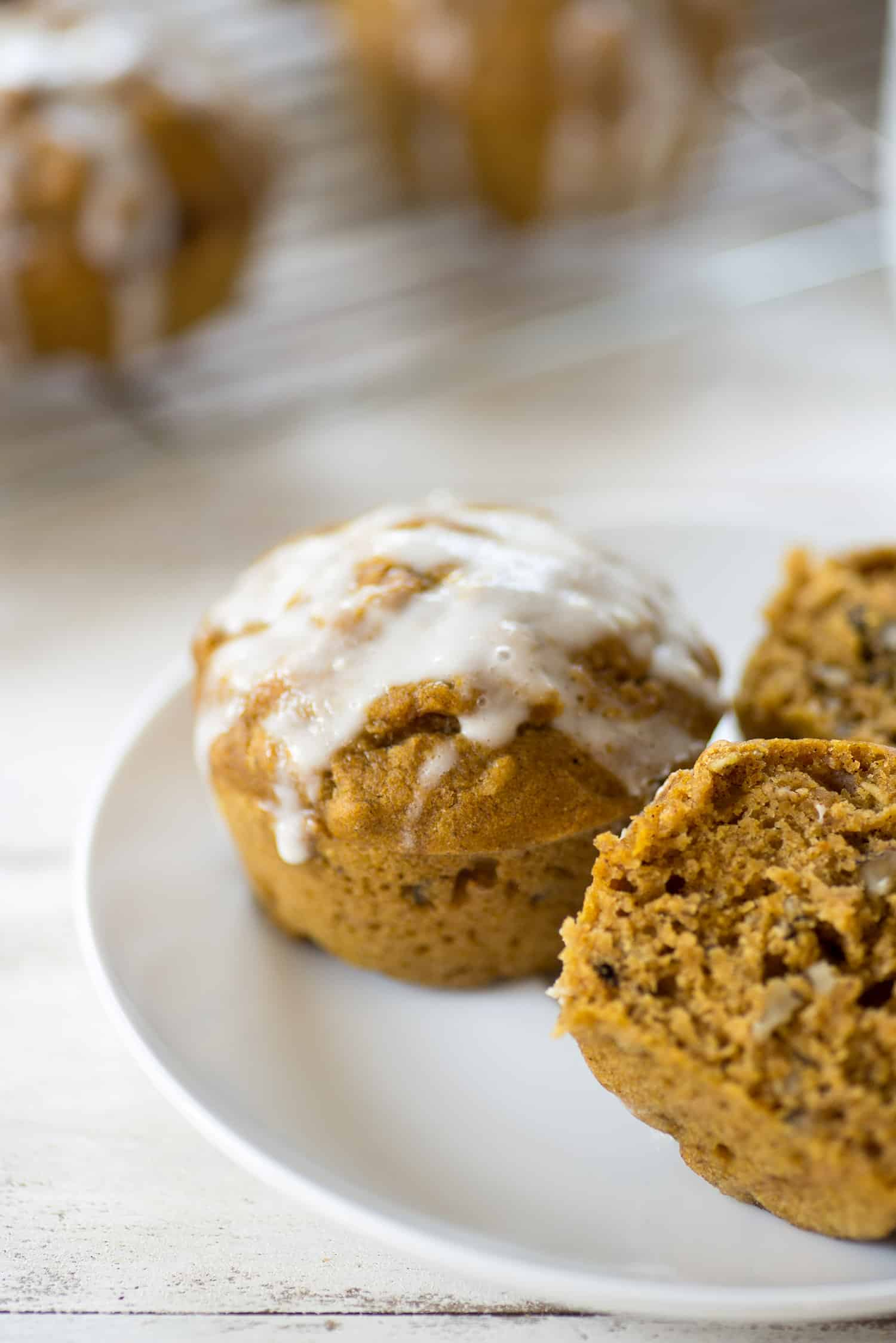 Pumpkin Muffins with Yogurt Glaze! These healthy, fiber-rich muffins are perfect for Fall. Topped with a homemade yogurt glaze. So delicious, perfect for school lunches and afternoon snacks!