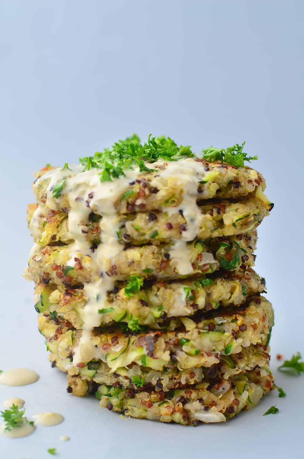 Greek Quinoa Zucchini Fritters! Crispy zucchini fritters with a garlic-hummus sauce. Perfect for leftover zucchini! | www.delishknowledge.com