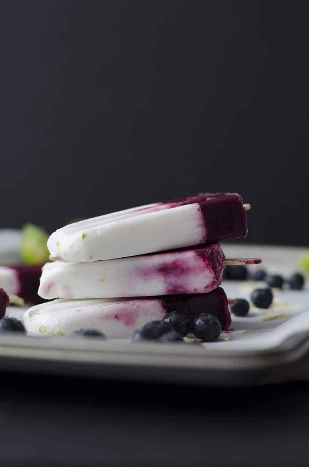 Roasted Blueberry, Coconut and Lime Popsicles! Roasting intensifies the sweetness of the berries, with very little added sugar. Layers of roasted blueberries, coconut and lime. Vegan & Gluten-Free | www.delishknowledge.com