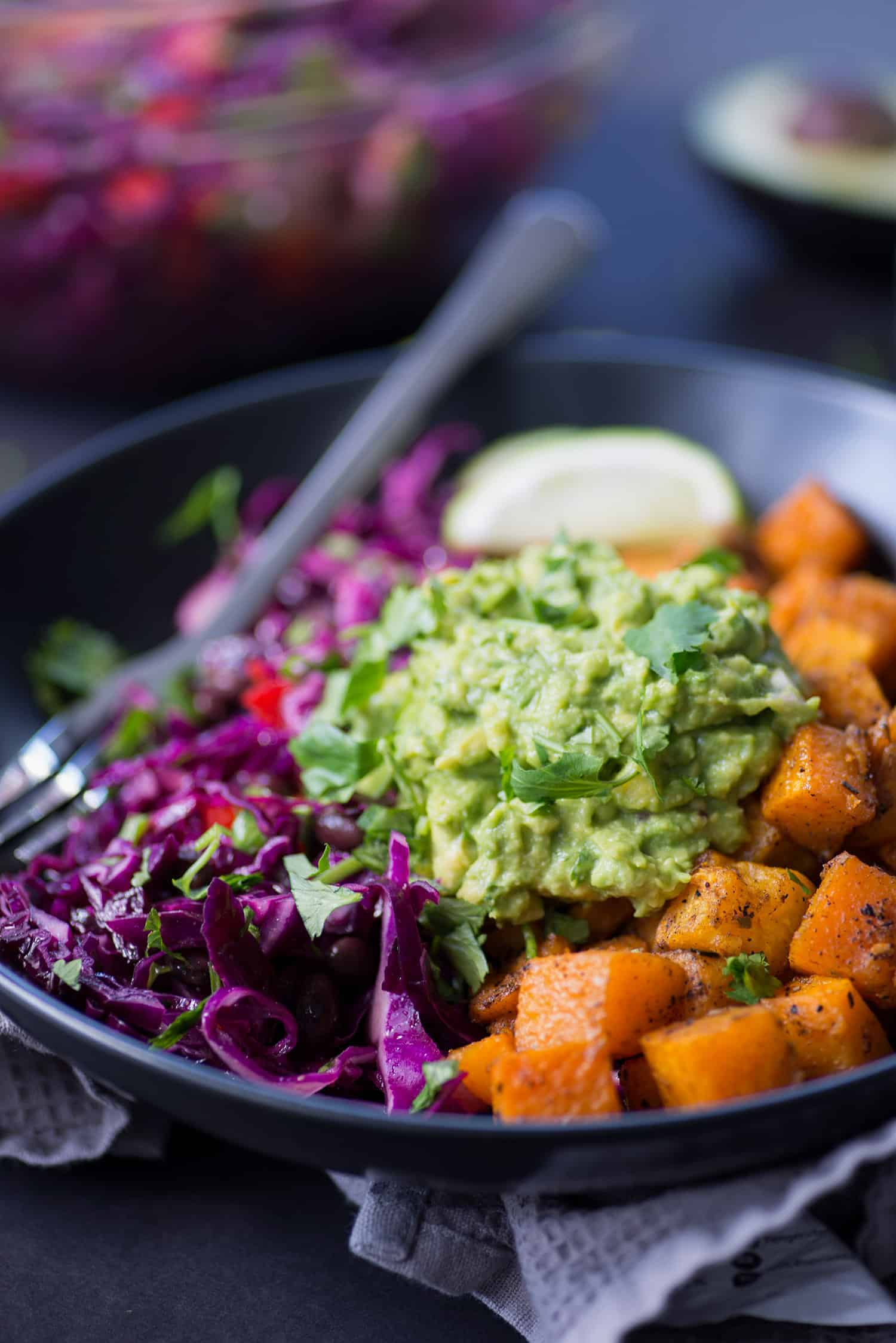 Roasted Butternut Squash Burrito Bowls! You will love these gluten-free and vegan burrito bowls. Roasted and spiced butternut squash cubes, black bean and cabbage slaw with homemade guacamole. Vegan & Gluten-Free | www.delishknowledge.com