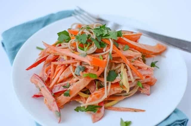 Vegan Sweet and Spicy Vegetable Noodles! Shredded carrots, peppers and soboa noodles in a spicy sauce.