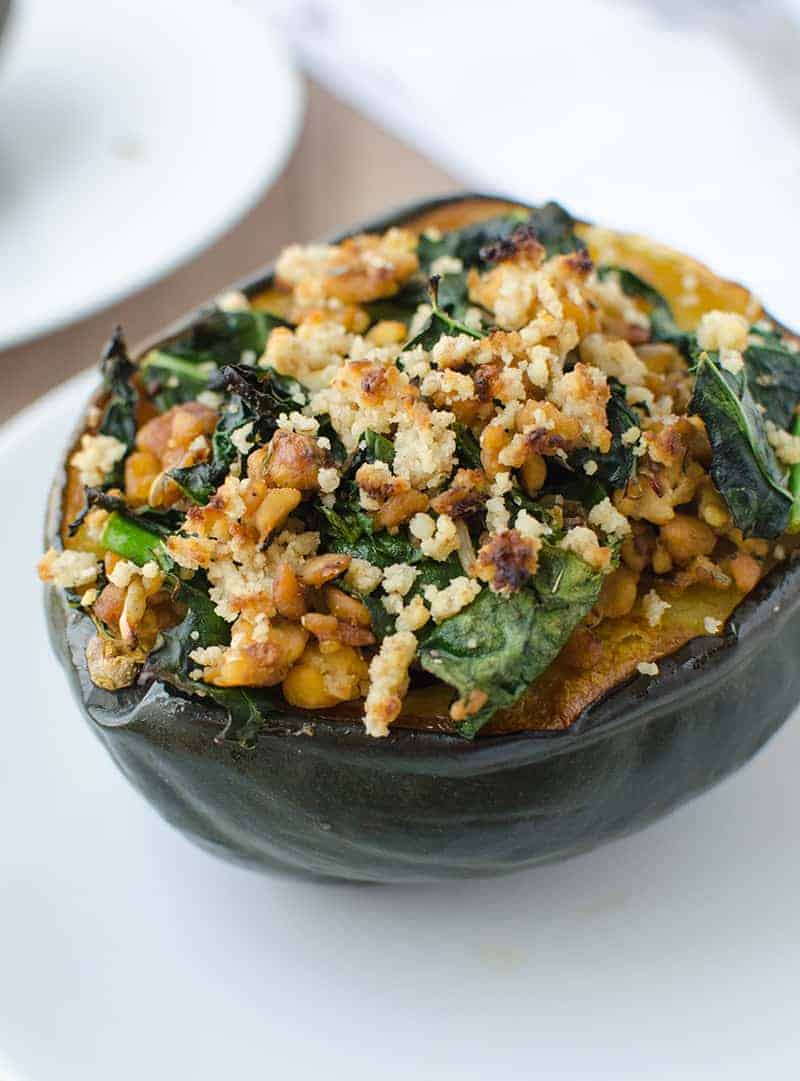 Stuffed Squash! The perfect centerpiece for Thanksgiving or Christmas. Vegan and gluten-free. Acorn squash stuffed with homemade temeph sausage, kale, and topped with a walnut crumble.   www.delishknowledge.com