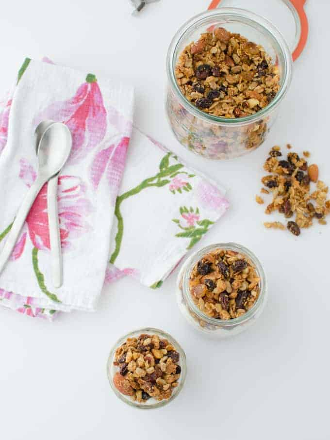 Trail mix granola! Healthy baked granola clusters of almonds, sunflower seeds, and walnuts. Layered in jars with frozen fruit and yogurt for a quick on-the-go breakfast! Vegan or vegetarian; gluten-free