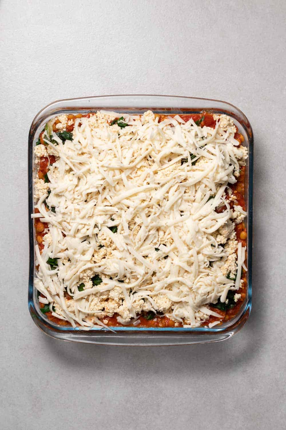 Adding freshly grated vegan cheese to the top of the lasagna