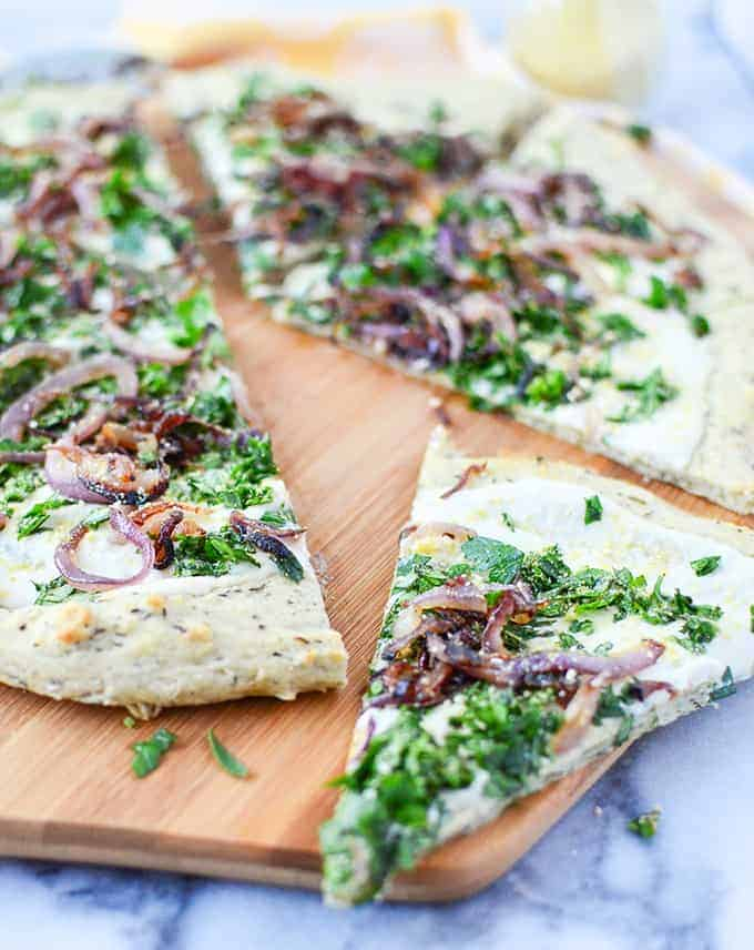 The best dairy-free pizza! Herb and garlic crust topped with creamy white sauce, caramelized onions, fresh herbs and vegan parm sprinkle.