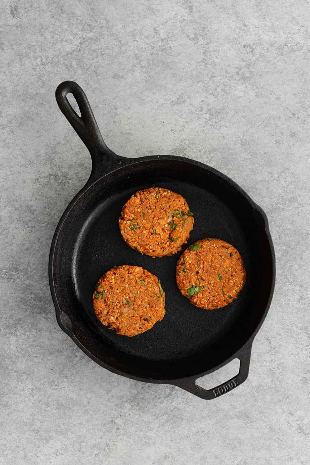 cast iron skillet with three sweet potato and black bean veggie burger patties