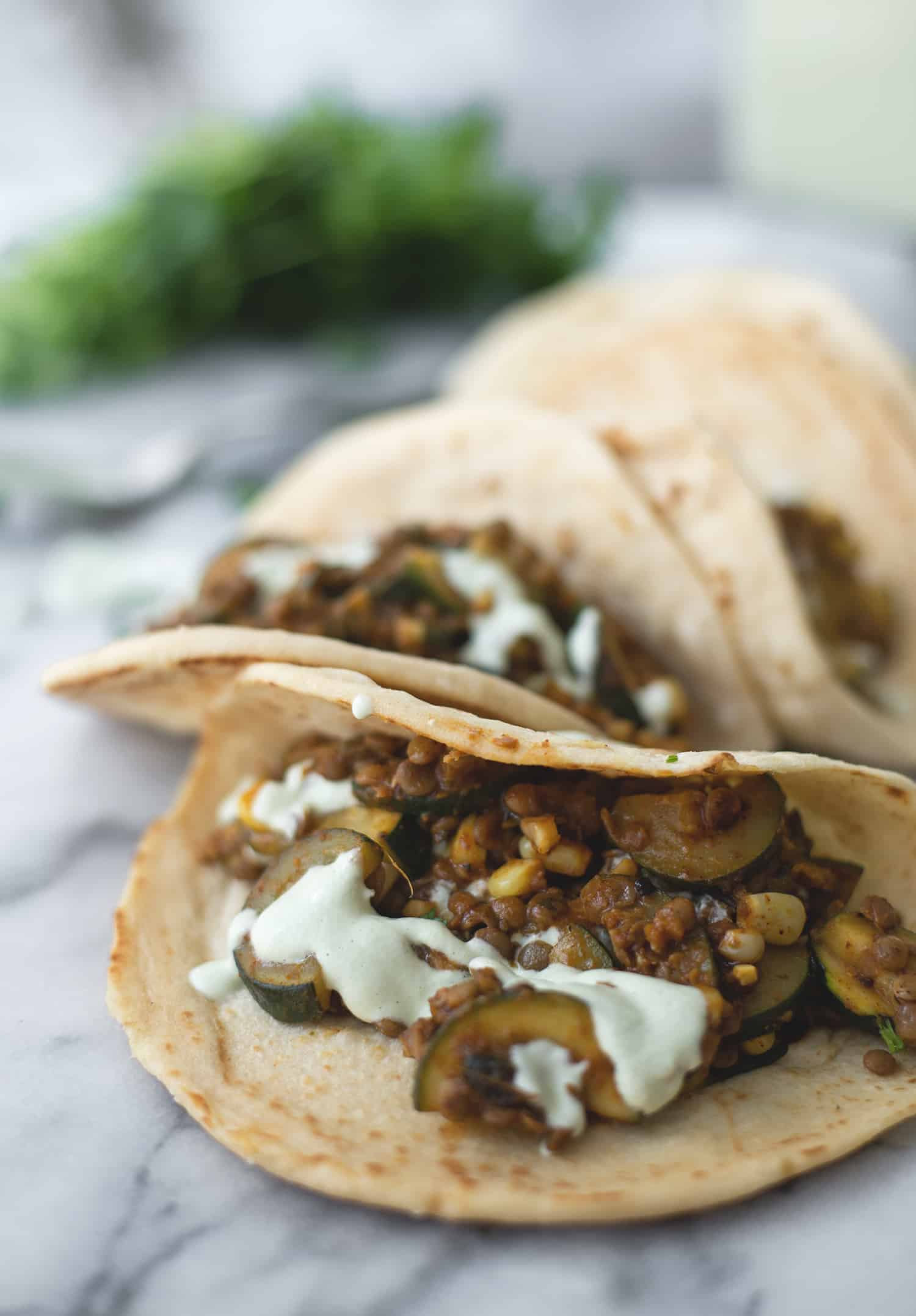Zucchini and Lentil Tacos! A perfect vegan dinner. Spicy zucchini and corn, lentils with a creamy jalapeno-lime sauce. | www.delishknowledge.com